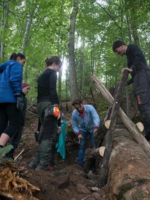 Teilnehmer des Waldprojekts bauen eine Holzkonstruktion.
