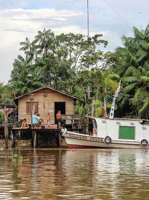 Menschen vor einer Hütte auf dem Wasser und Boot.