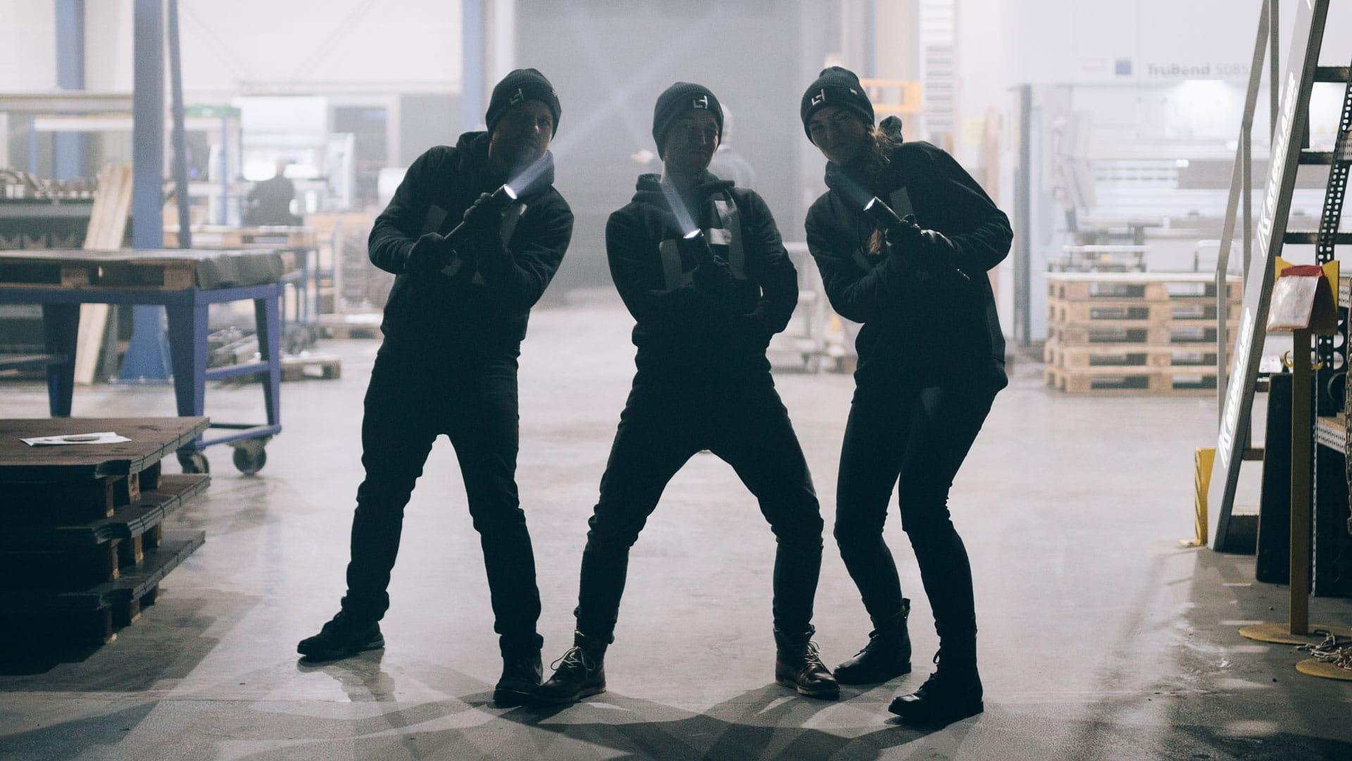Drei MitarbeiterInnen von Laserhub in Einbruchsmontier stehen in einer Fabrikhalle.